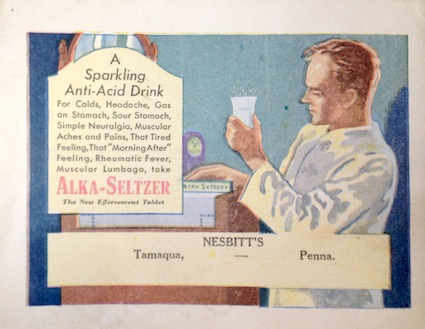 A staid, clean-cut scientist inspects a glass of Alka-Seltzer.